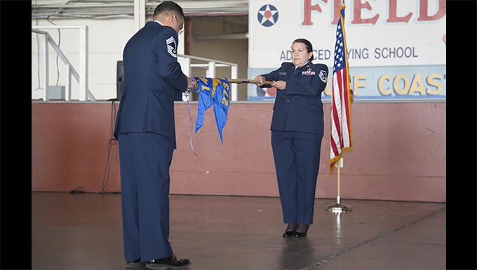 Chief Master Sgt. Albert Salinas, superintendent of the 273rd Cyber Operations Squadron, reveals the new COS guidon held by Master Sgt. Marcelina Morales, 1st Sgt. for the 273rd COS, during a re-designation ceremony at Port San Antonio's Heritage Hangar Jan. 6, 2018. (Air National Guard by Senior Master Sgt. Robert Shelley)
