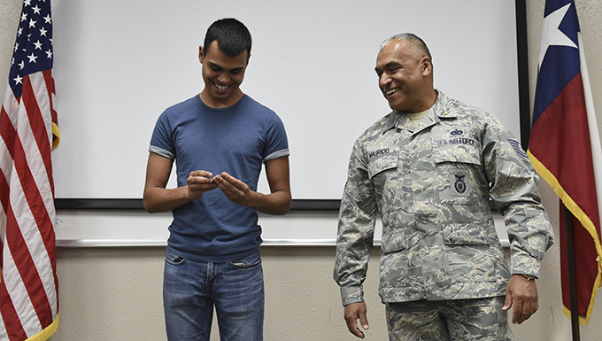 Tech. Sgt. Manuel Mauricio retires from the 149th SFS during a joint enlistment and retirement ceremony on the same day his son Nathaniel Mauricio enlists into the unit.